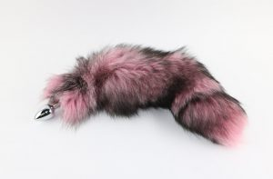 Picture of indigo fox tail dyed light pink from Spank Academy website. Tail is pink with black accents and attached to a stainless steel plug.