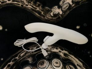 Satisfyer toy lying on blanket with charger