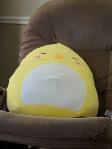 Giant chicken squishmallow on a chair