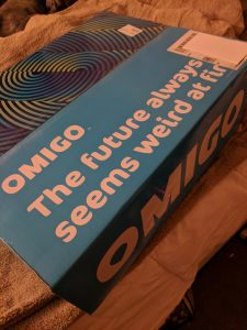 "Omigo box, which says ""the future always seems weird at first"" in white letters on a blue background"