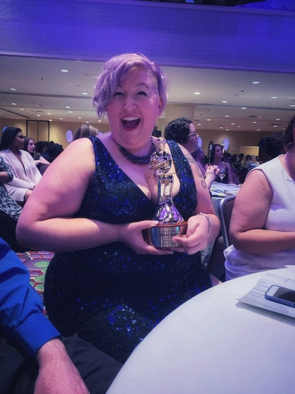 Me, grinning broadly while holding my RITA statue back at the table